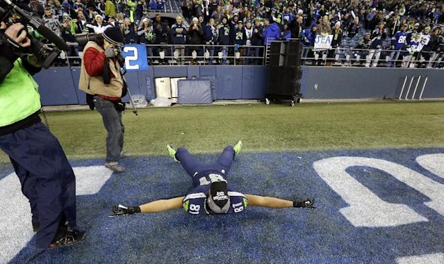 Seattle Seahawks' Golden Tate lies on the field and motions to fans after the team beat the St. Louis Rams in an NFL football game, Sunday, Dec. 29, 2013, in Seattle. The Seahawks won 27-9. (AP Photo/Elaine Thompson)