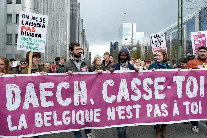 """People hold a banner reading """"Daesh, off you go, Brussels isn't for you"""" in reference to the Islamic State group during a march in tribute to victims of the Brussels attacks and against violence in Brussels on April 17, 2016 (AFP Photo/Thierry Charlier)"""