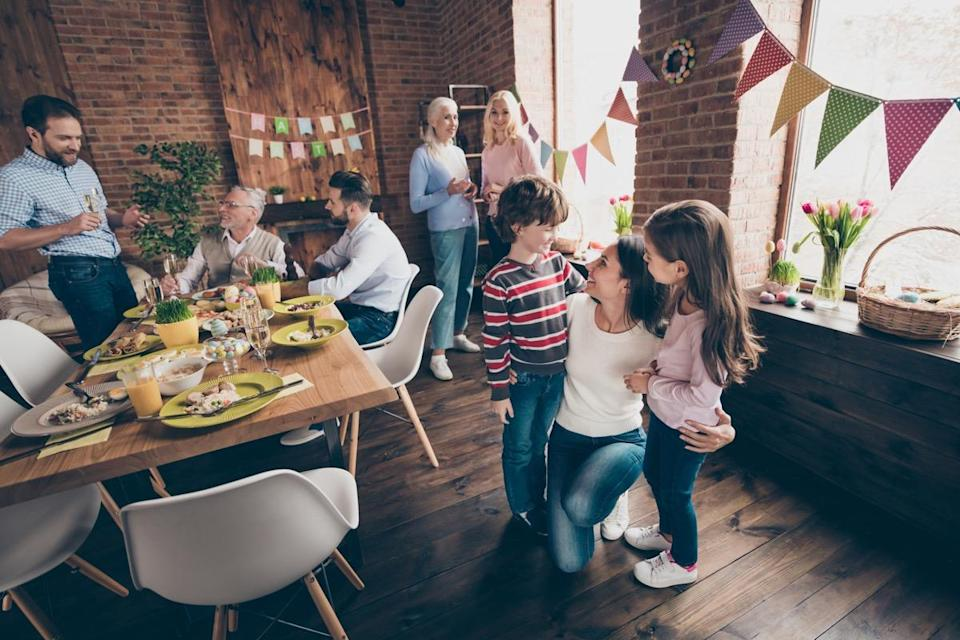 Gathered relatives in decorated house dinner table mom embrace little girl boy children listen to congratulations other communicate talk tell speak