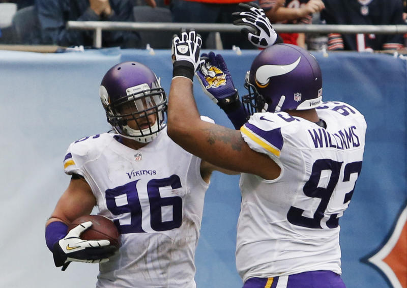 Minnesota Vikings defensive end Brian Robison (96) celebrates with teammate Kevin Williams (93) after scoring a touchdown on a fumble recovery against the Chicago Bears during the first half of an NFL football game on Sunday, Sept. 15, 2013, in Chicago. (AP Photo/Charles Rex Arbogast)