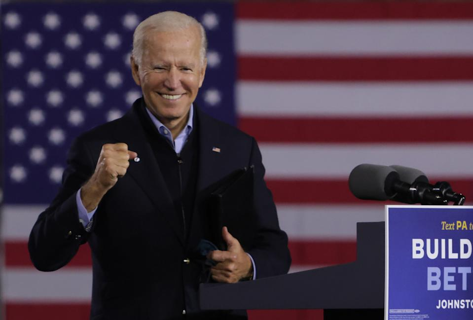 Joe Biden smiles at a podium in front of an American flag