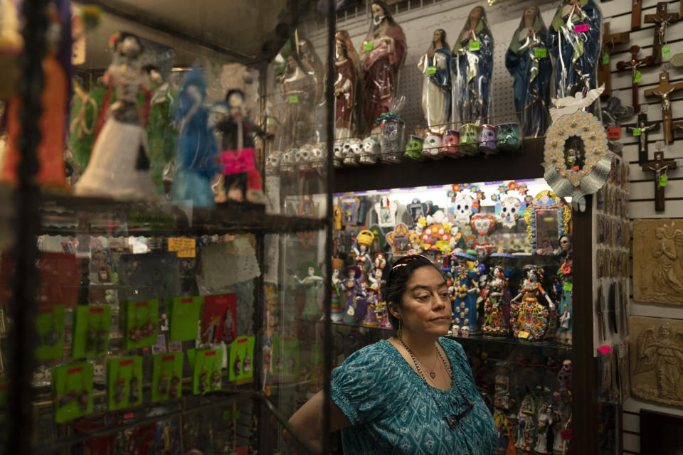 """Valerie Hanley, owner of Casa California souvenir shop on Olvera Street and treasurer of the Olvera Street Merchants Association Foundation, stands for a photo in her shop in Los Angeles, Friday, June 4, 2021. Most businesses are no longer open daily and many have cut back to four or five days, said Hanley. """"We're not like a local restaurant in your town,"""" Hanley said. """"We're one of those little niche things. If you can't fill the niche with the right people, we're in trouble."""" (AP Photo/Jae C. Hong)"""