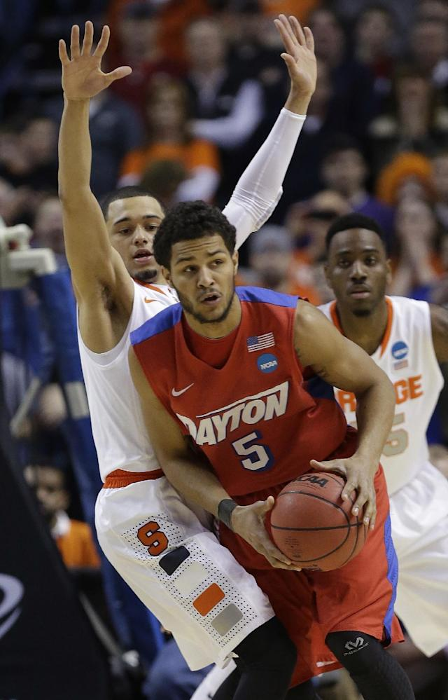 Dayton's Devin Oliver (5) passes away from Syracuse's Tyler Ennis during the first half of a third-round game in the NCAA men's college basketball tournament in Buffalo, N.Y., Saturday, March 22, 2014. (AP Photo/Frank Franklin II)
