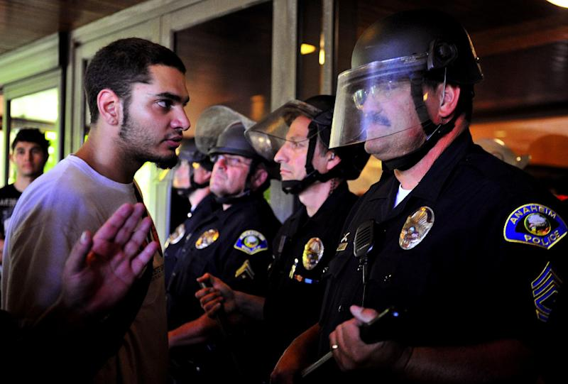 Demonstrators gather on the steps of Anaheim City Hall Tuesday, July 24, 2012, to protest the death of Manuel Diaz, 25, who died as a result of gunshot wounds sustained during a police pursuit by the Anaheim Police Department last Saturday. As many as 500 protesters and 250 police were involved in a fourth night of violence Tuesday. Seven hours of confrontations ended around 2 a.m. Wednesday. (AP Photo/The Orange County Register,Stuart Palley ) MAGS OUT; LOS ANGELES TIMES OUT