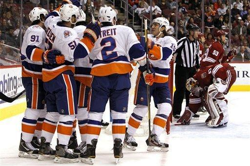 New York Islanders' Frans Nielsen (51), of Denmark, celebrates his goal with teammates John Tavares (91), Mark Streit (2) and P.A. Parenteau (15) as Phoenix Coyotes' Mike Smith (41) and Derek Morris (53) look away during the first period in an NHL hockey game on Saturday, Jan. 7, 2012, in Glendale, Ariz. (AP Photo/Ross D. Franklin)