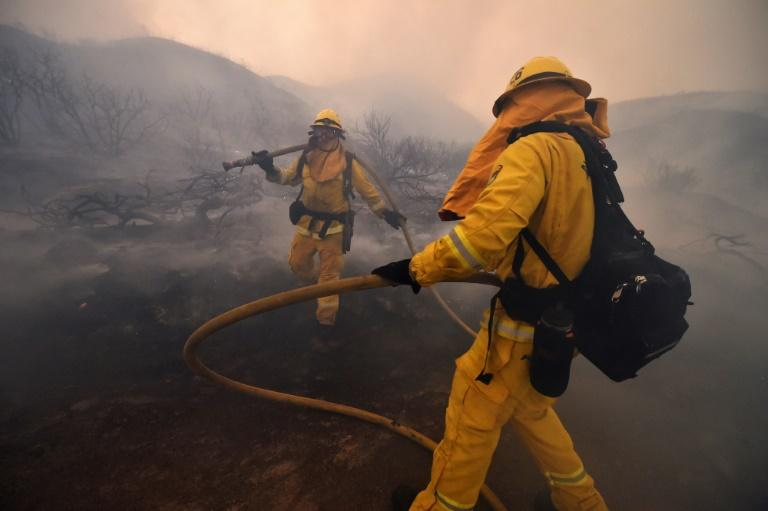 Riverside County firefighters douse embers after flames tore down a hillside in a residential neighborhood during the Holy Fire in Lake Elsinore, California, on August 9, 2018