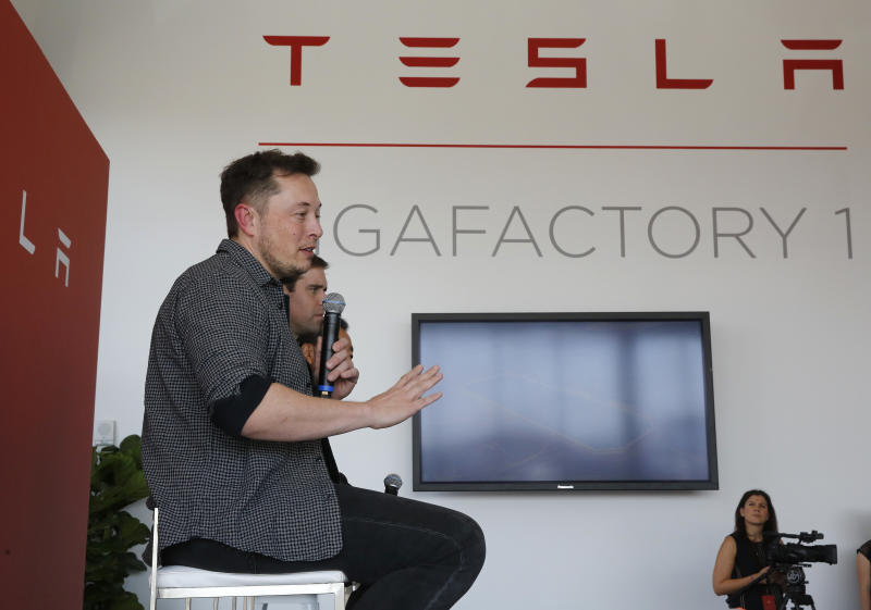 Elon Musk, CEO of Tesla Motors Inc., left, discusses the company's new Gigafactory Tuesday, July 26, 2016, in Sparks, Nev. It's Tesla Motors biggest bet yet: a massive, $5 billion factory in the Nevada desert that could nearly double the world's production of lithium-ion batteries by 2018. In the center is J.B. Straubel, Tesla's chief technical officer and at right is Yoshihiko Yamada, executive vice president of Panasonic. (AP Photo/Rich Pedroncelli)