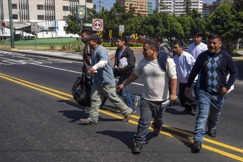 Guatemalan men who were deported from the United States cross a street after arriving in Guatemala City, Thursday, Nov. 21, 2019. Guatemala's Foreign Ministry said a Honduran asylum seeker has also been returned by the United States to pursue asylum in Guatemala for the first time under an agreement signed in July. The Honduran man, who was not identified, had reached the U.S. border but was sent to Guatemala Thursday. (AP Photo/Moises Castillo)