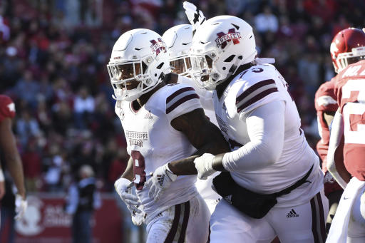 Mississippi State running back Kylin Hill (8) celebrates with teammate Darryl Williams (73) after scoring a touchdown against Arkansas during the first half of an NCAA college football game, Saturday, Nov. 2, 2019, in Fayetteville, Ark. (AP Photo/Michael Woods)