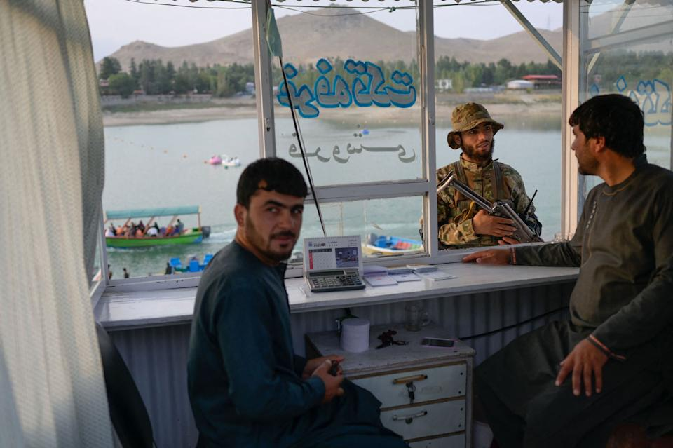 A Taliban member (middle) speaks with shop owners at Qargha Reservoir on the outskirts of Kabul on September 19. Source: Getty Images