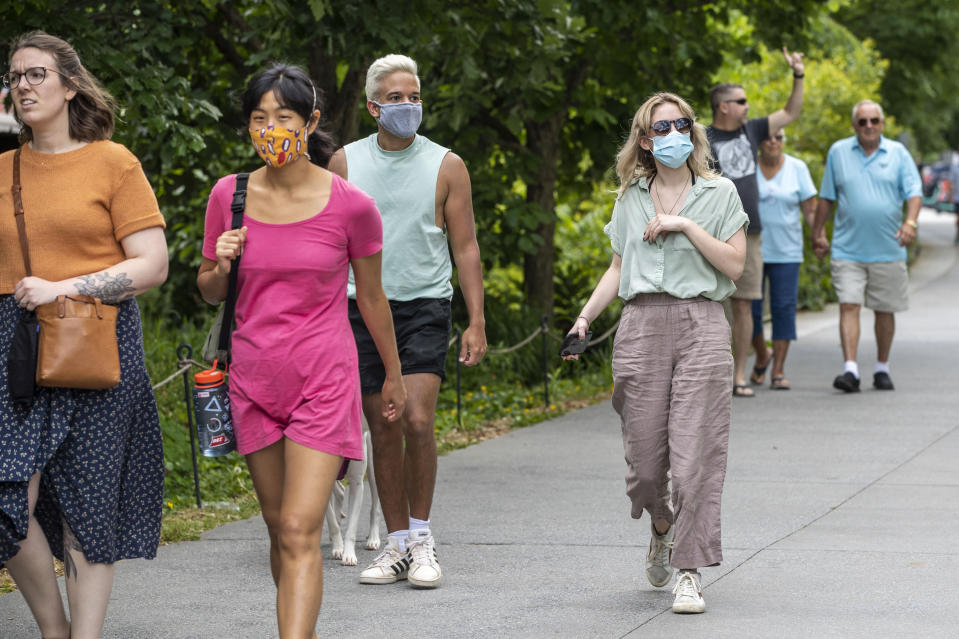 Madeline Raskay, right, and Aldany Diaz, third from left, wear face masks while walking along the Atlanta BeltLine in Atlanta's Old Fourth Ward community, Friday, May 14, 2021. Both of them say they are fully vaccinated but still prefer to wear face masks in while out in public. (Alyssa Pointer/Atlanta Journal-Constitution via AP)