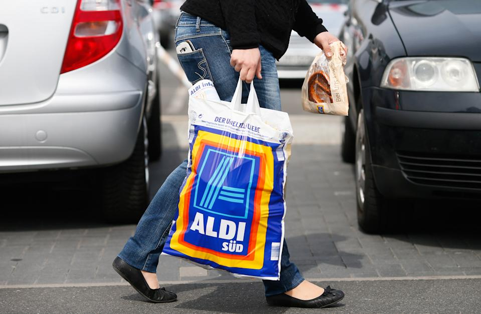 RUESSELSHEIM, GERMANY - APRIL 8:   A shopper carries a bag outside an Aldi store on April 8, 2013 in Ruesselsheim near Frankfurt, Germany. Aldi, which today is among the world's most successful discount grocery store chains, will soon mark its 100th anniversary and traces its history back to Karl Albrecht, who began selling baked goods in Essen on April 10, 1913 and founded the Aldi name by shortening the phrase Albrecht Discount. His sons Karl Jr. and Theo expanded the chain dramatically, creating 300 stores by 1960 divided between northern and southern Germany, with Aldi Nord and Aldi Sued, respectively. Today the two chains have approximately 4,300 stores nationwide and have also expanded into other countries across Europe and the USA. Aldi Nord operates in the USA under the name Trader Joe's. (Photo by Ralph Orlowski/Getty Images)
