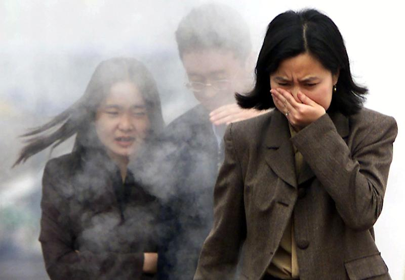 People cover their noses to avoid a foul smell (AFP Photo/)
