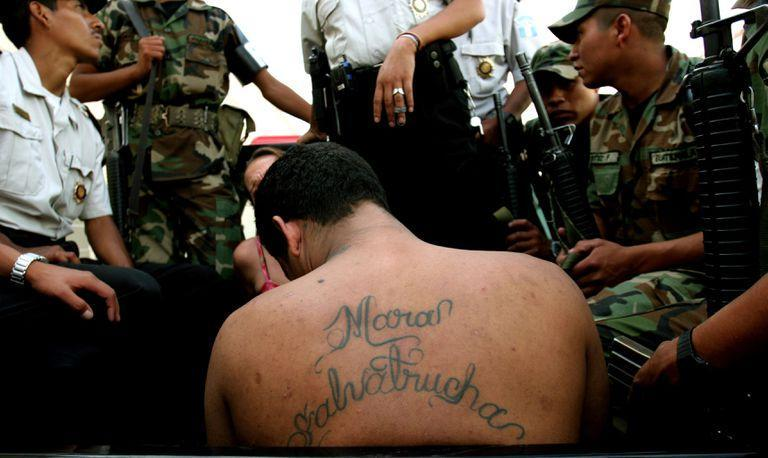 """A gang member of the Mara Salvatrucha gang is detained by army and police in Guatemala City, July 20, 2005. A string of violent and mysterious killings targeting gang members and criminals in Guatemala has prompted rumors of a """"social cleansing,"""" an effort to weed out undesirable members of society. Some blame police, others point a finger at vigilante groups sick of rising crime. Police say rival gangs are responsible. (AP Photo/Rodrigo Abd)"""