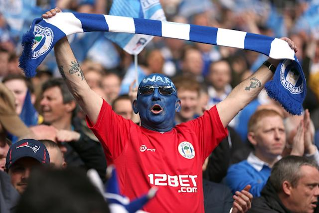 A Wigan Athletic fan shows his support in the stands
