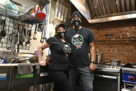 Owners of The Black Italian restaurant and catering service, Paula Hunter, left, and her husband Anthony Hunter in their empty restaurant in Louisville, Ky., Thursday, Dec. 3, 2020. The Hunter's spun off their catering service into a restaurant but now, hit with a recent statewide order closing restaurants to indoor dining until mid-December, the couple is hoping for another round of federal aid to hang on until vaccines can conquer the virus. (AP Photo/Timothy D. Easley)