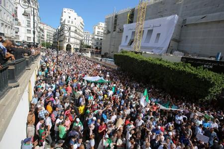 Demonstrators carry national flags and banners during a protest against a proposed new hydrocarbons law in Algiers