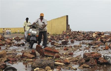 People walk among debris from a broken wall after it was damaged by a wave brought by Cyclone Phailin at a fishing harbour in Visakhapatnam district in Andhra Pradesh October 12, 2013. REUTERS/R Narendra