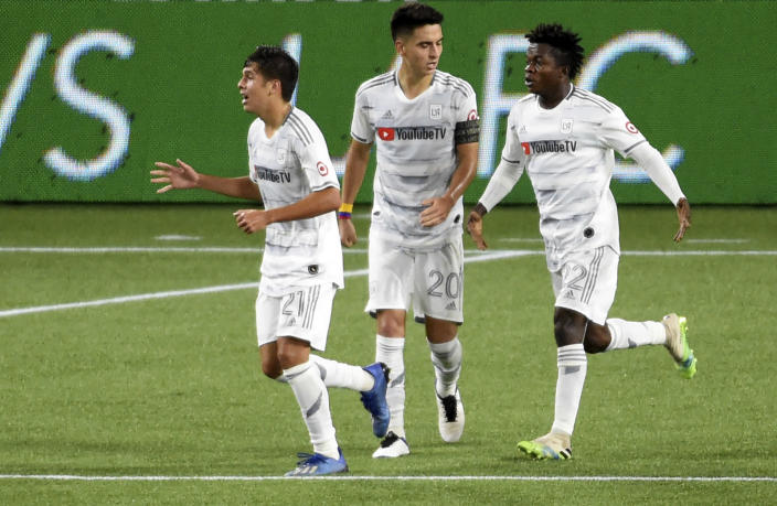 Los Angeles FC forward Christian Torres, left, celebrates with teammates midfielder Eduard Atuesta, center, and Los Angeles FC forward Kwadwo Opoku, right, after scoring a goal in stoppage time during the second half of an MLS soccer match against the Portland Timbers in Portland, Ore., Sunday, Oct. 18, 2020. The match ended in a 1-1- draw. (AP Photo/Steve Dykes)
