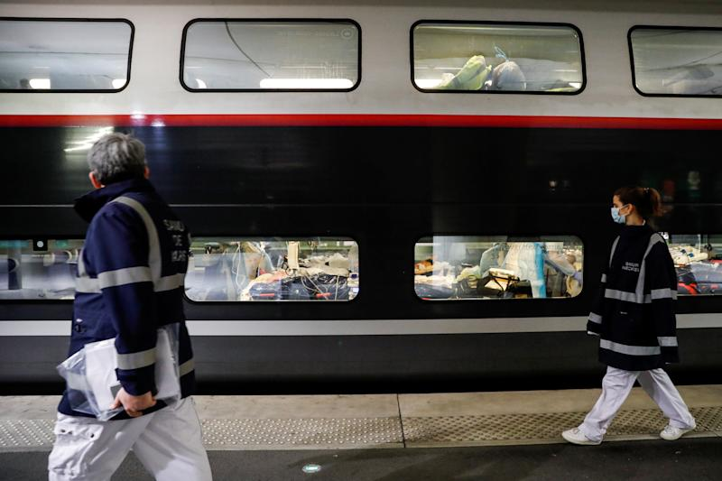 Staff walk past a TGV loaded with people infected by the coronavirus. (Thomas Samson/Pool via REUTERS)
