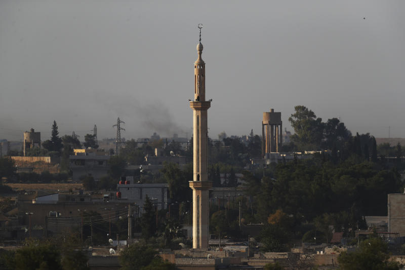 In this photo taken from the Turkish side of the border between Turkey and Syria, in Akcakale, Sanliurfa province, southeastern Turkey, the town of Tel Abyad can be seen inside Syria, Saturday, Oct. 12, 2019. (AP Photo/Lefteris Pitarakis)