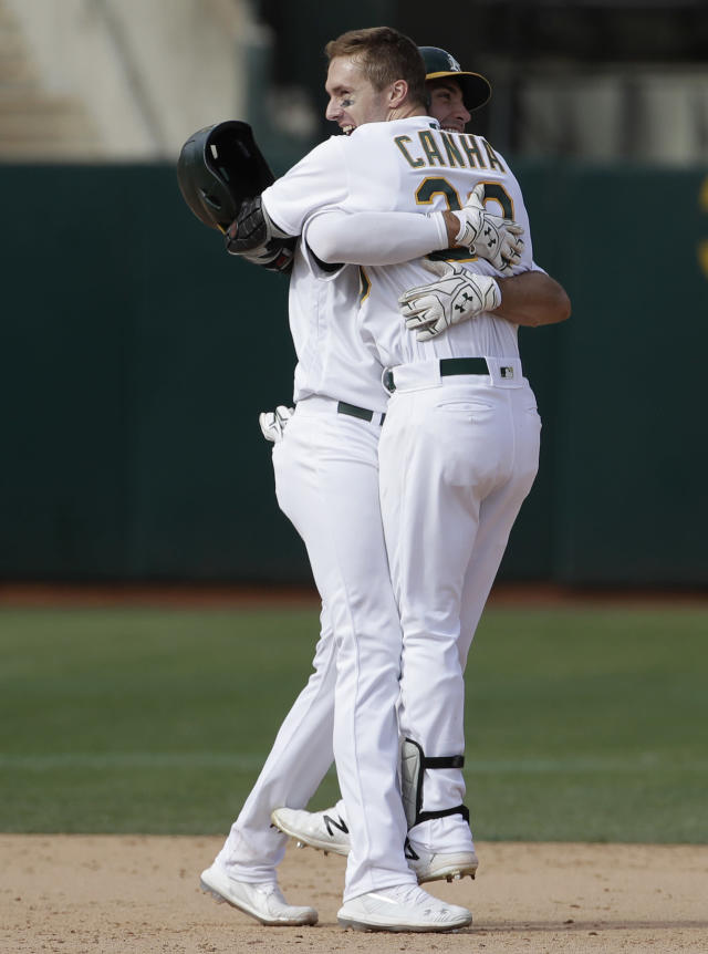Oakland Athletics' Mark Canha, right, celebrates with Matt Olson after the Athletics defeated the Kansas City Royals 1-0 in 11 innings of a baseball game in Oakland, Calif., Wednesday, Sept. 18, 2019. Canha hit a double to score Jurickson Profar. (AP Photo/Jeff Chiu)