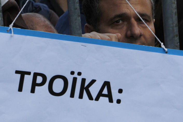 """A protestor is seen behind a banner that reads in Greek """"Troika"""" on a barricade outside of Parliament during a strike to protest government plans to privatize the state-run organizations in Nicosia, Cyprus, Thursday, Feb. 27, 2014. Hundreds of protesters have gathered outside Cyprus' parliament to voice opposition against legislation that will pave the way for the privatization of state-owned companies. (AP Photo/Petros Karadjias)"""