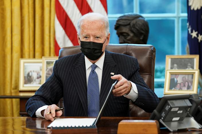 President Biden, wearing a black face mask, signs an exectutive order at a desk