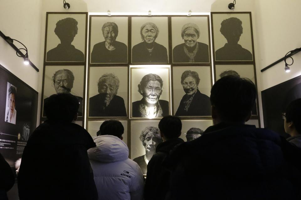 """South Korea high school students look at portraits of late former """"sex salves"""" who were forced to serve for the Japanese Army during World War II at the House of Sharing, the home for the living sex slaves, in Gwangju, South Korea, Tuesday, Dec. 29, 2015. A day after trumpeting an """"irreversible"""" settlement of a decades-long standoff over Korean women forced into sexual slavery by Japan's WWII military, there's relief among South Korean and Japanese diplomats, fury among activists and many of the elderly victims and general public indifference in both countries. (AP Photo/Ahn Young-joon)"""