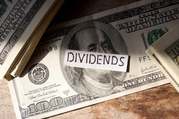 """$100 bills with the word """"dividends"""" on top."""