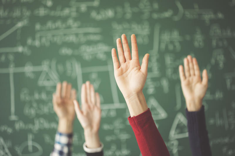 Hands are raised in front of a blackboard.
