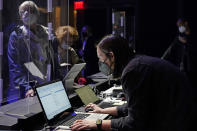 Concertgoers are protected behind plastic protectors as an employee checks her computer for their reservations before the start of a performance by the New York Philharmonic at The Shed in Hudson Yards, Wednesday, April 14, 2021, in New York. It was the first time the Philharmonic had performed together for a live audience since March 10, 2020. (AP Photo/Kathy Willens)