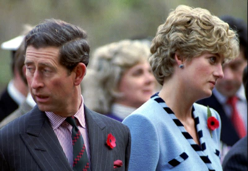 FILE PHOTO: Princess Diana and Prince Charles look in different directions, November 3, during a service