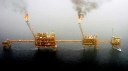Gas flares from an oil production platform at the Soroush oil fields in the Persian Gulf, south of the capital Tehran, July 25, 2005. REUTERS/Raheb Homavandi/Files
