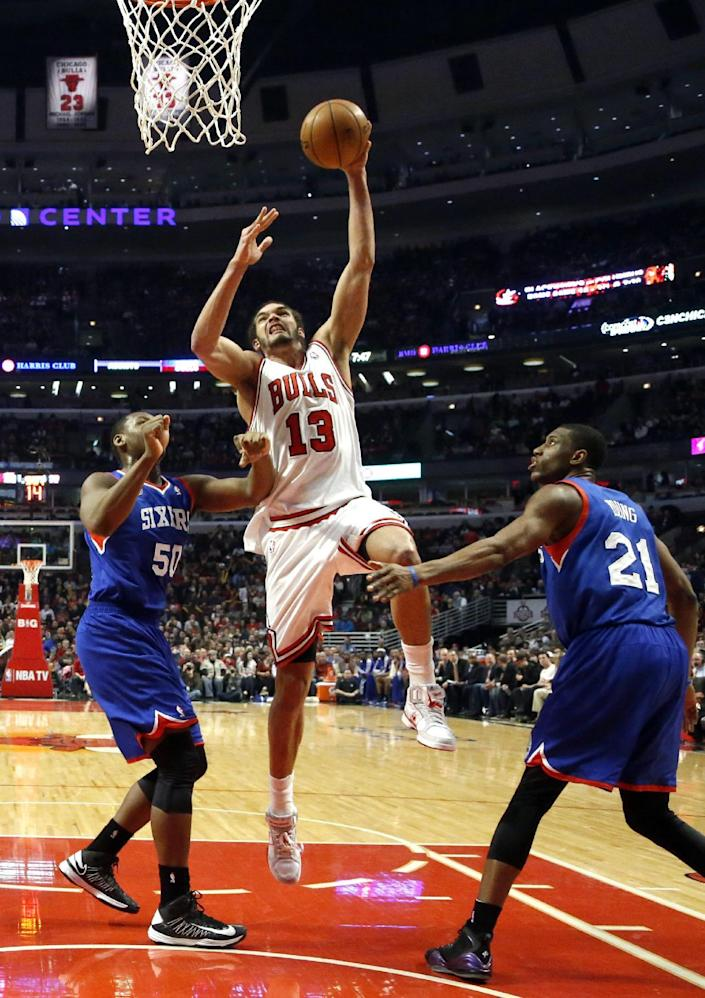 Chicago Bulls center Joakim Noah (13) goes up for a dunk between Philadelphia 76ers forward Lavoy Allen (50) and Thaddeus Young during the first half of an NBA basketball game, Thursday, Feb. 28, 2013, in Chicago. (AP Photo/Charles Rex Arbogast)