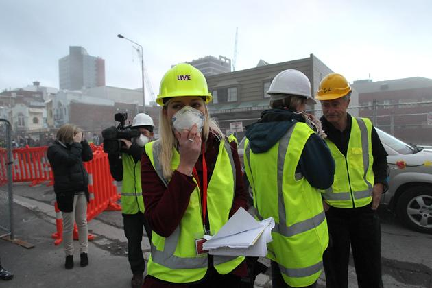 CHRISTCHURCH, NEW ZEALAND - AUGUST 05: Journalists react to dust after a controlled explosion on August 5, 2012 in Christchurch, New Zealand. The 14-story Radio Network House building in Worcester St, is the first of its kind in the city to be blown up in a controlled demolition since authorities began the massive task of bringing down the hundreds of quake-damaged buildings. The building was badly damaged in the magnitude-6.3 February 22, 2011 earthquake.  (Photo by Martin Hunter/Getty Images)