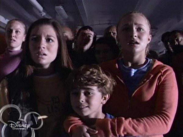 The kids stare in horror at the TV as the twin towers get hit.