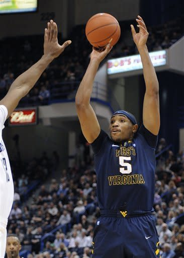 West Virginia's Kevin Jones (5) takes a 3-pointer during the first half of an NCAA college basketball game against Connecticut in Hartford, Conn., on Monday, Jan. 9, 2012. (AP Photo/Fred Beckham)