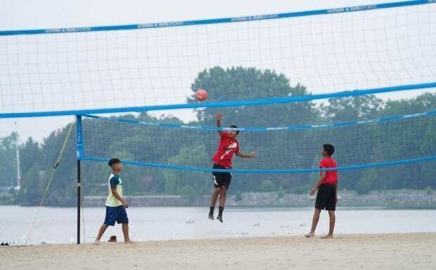 A trio of volleyball players play at Britannia Beach in Ottawa on Tuesday, July 20, 2021.  (Sean Kilpatrick/The Canadian Press - image credit)