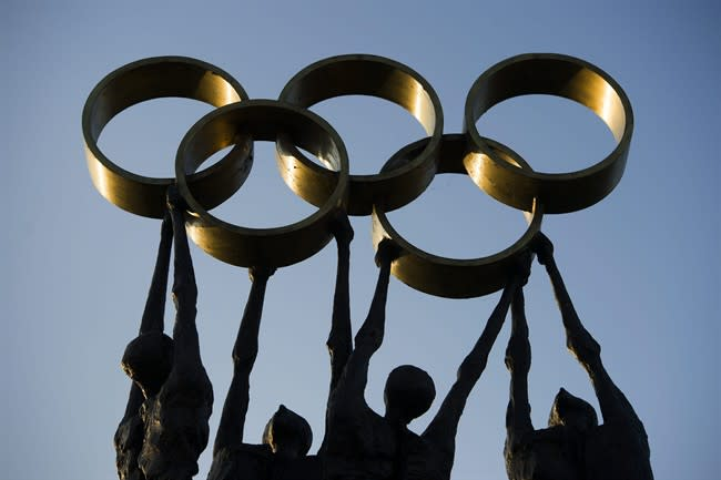 The sun is reflected in a statue with the Olympic rings during the executive board's meeting, next to the IOC headquarters, in Lausanne, Switzerland, Tuesday, Dec. 10, 2013. (AP Photo/Keystone,Jean-Christophe Bott)