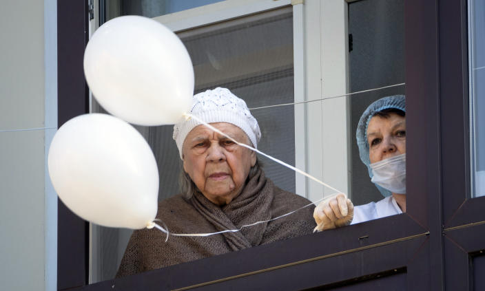 An elderly resident of a House of War and Labor Veterans and a medical worker, who cannot go outside to celebrate Victory Day due to coronavirus, watches a march of members Yunarmia (Young Army), an organization sponsored by the Russian military that aims to encourage patriotism among the Russian youth, in St.Petersburg, Russia, Saturday, May 9, 2020. Victory Day, the anniversary of the defeat of Nazi Germany in World War II, is Russia's most important secular holiday and this year's observance had been expected to be especially large because it is the 75th anniversary, but military parades in Russian cities and a mass processions called The Immortal Regiment were postponed as part of measures to stifle the spread of the virus. (AP Photo/Dmitri Lovetsky)