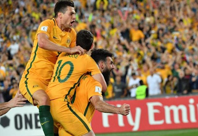Australia's Mile Jedinak (R) is congratulated by teammates after scoring a goal against Honduras in their FIFA 2018 World Cup qualification play-off 2nd leg match, in Sydney, on November 15, 2017