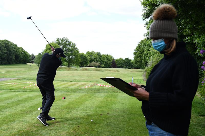 A golfer wearing a face mask practises teeing off, watched by starter Wendy (no surname given), at the Hampstead Golf Club in north London, after the announcement of plans to bring the country out of lockdown. (Photo by Kirsty O'Connor/PA Images via Getty Images)