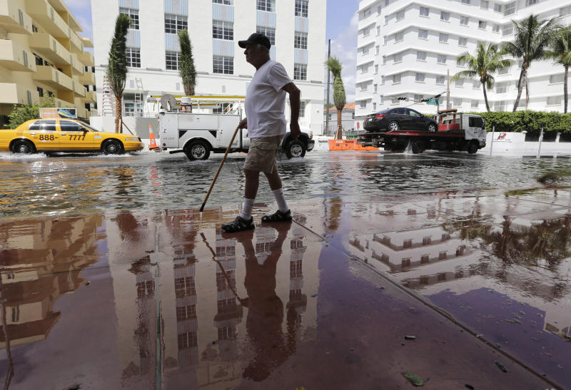 FILE- In this Sept. 30, 2015 file photo, Louis Fernandez walks along a flooded street in Miami Beach, Fla. The street flooding was in part caused by high tides due to the lunar cycle, according to the National Weather Service. When Democratic presidential candidates meet in Miami for their first debate it'll be in what you could call the country's Ground Zero for any climate-related sea level rise. (AP Photo/Lynne Sladky, File)