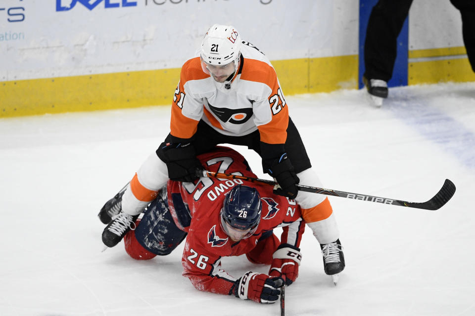 Philadelphia Flyers center Scott Laughton (21) stands over Washington Capitals center Nic Dowd (26) during the first period of an NHL hockey game Saturday, May 8, 2021, in Washington. (AP Photo/Nick Wass)