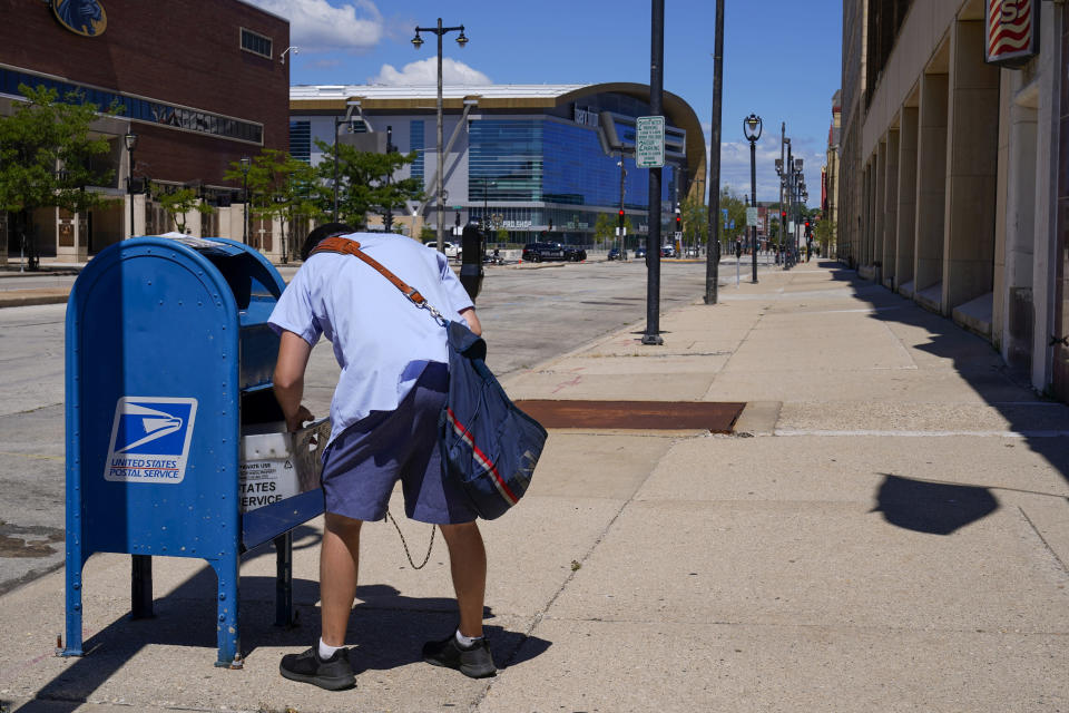 A postal worker empties a box near the Fiserv Forum on Tuesday, Aug. 18, 2020, in Milwaukee. With the Trump administration openly trying to undermine mail-in voting this fall, some election officials around the country are hoping to bypass the Postal Service by installing lots of ballot drop boxes in libraries, community centers and other public places. (AP Photo/Morry Gash)