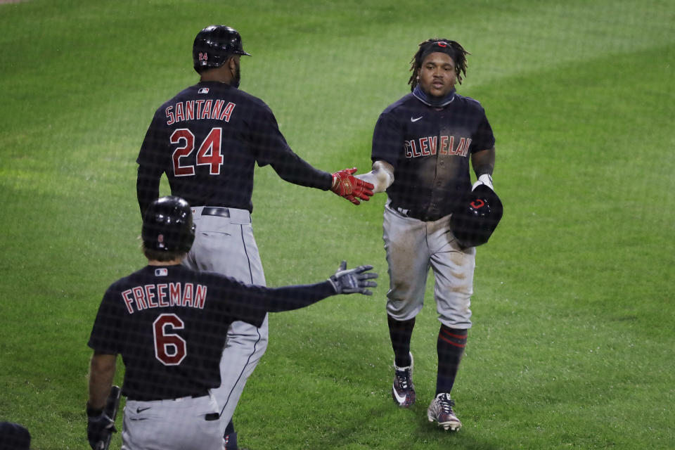Cleveland Indians' Jose Ramirez, right, celebrates with Domingo Santana (24) and Mike Freeman after scoring on a sacrifice bunt by Delino DeShields during the 10th inning of the team's baseball game against the Chicago White Sox in Chicago, Sunday, Aug. 9, 2020. (AP Photo/Nam Y. Huh)