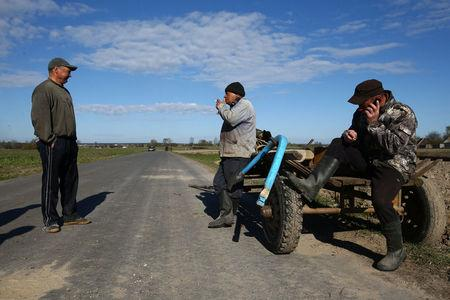 Vladimir Krivenchik (C), 65, smokes a cigarette as he takes a break with other villagers at a field in the village of Khrapkovo, Belarus, April 24, 2017. REUTERS/Vasily Fedosenko
