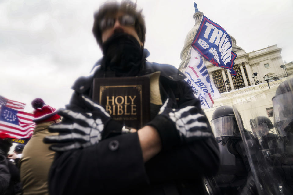 FILE - In this Wednesday, Jan. 6, 2021 file photo, a man holds a Bible as Trump supporters gather outside the Capitol in Washington. The Christian imagery and rhetoric on view during this month's Capitol insurrection are sparking renewed debate about the societal effects of melding Christian faith with an exclusionary breed of nationalism. (AP Photo/John Minchillo)