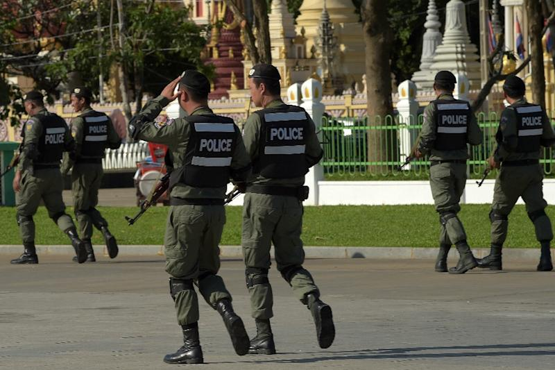 Cambodian police officials patrol during a hearing at the Supreme Court in Phnom Penh (AFP Photo/TANG CHHIN SOTHY)